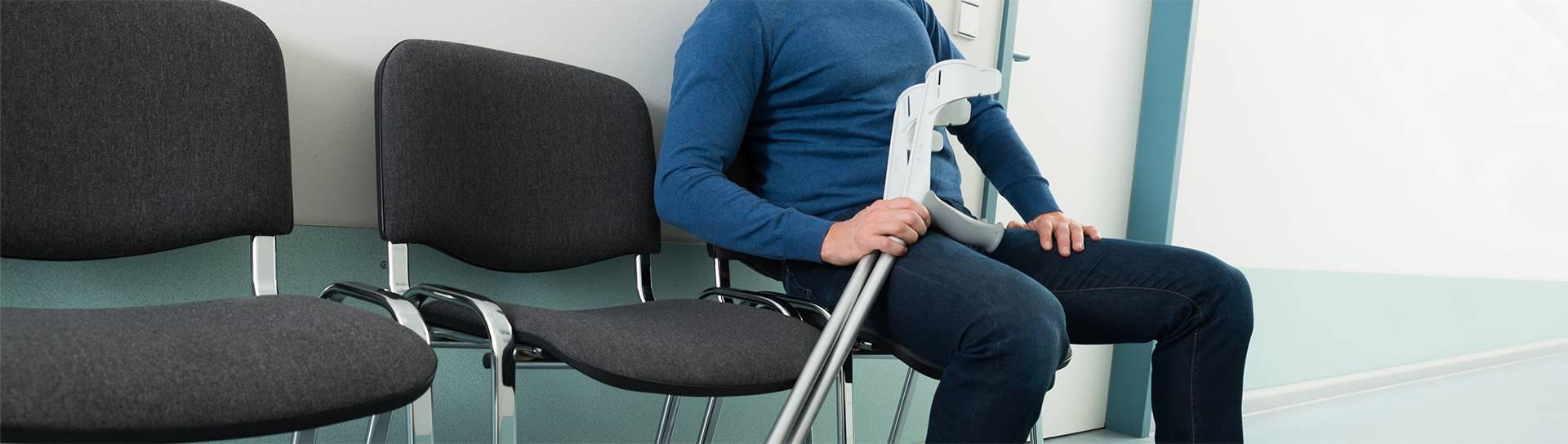 אדם עם קביים ממתין לרופא